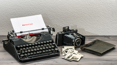retro typewriter and vintage photo camera on wooden table  White paper page with sample text Memories photo