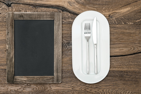 blackboard for menu on wooden table with white plate and silverware  space for your text and recipes photo