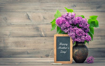 bouquet of lilac flowers in vase on wooden background  blackboard with sample text Happy Mother