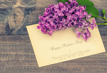 greeting cards: lilac flowers on wooden background  greeting card with sample text Happy Mother Stock Photo