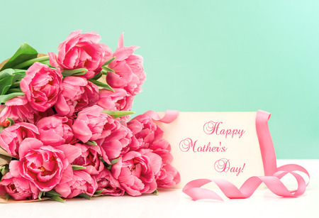 water s: Pink tulips and greeting card with sample text Happy Mother