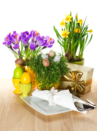 festive easter table setting with spring flowers and eggs decoration on white background photo