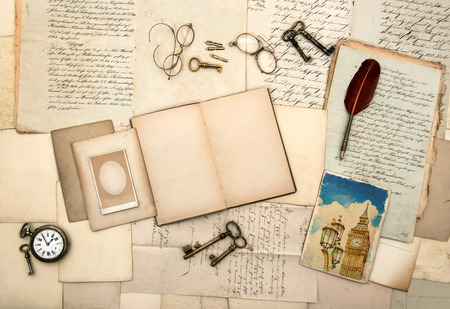 open travel diary book, picture from london, vintage accessories, old letters, post cards, glasses, keys, clock  nostalgic background photo