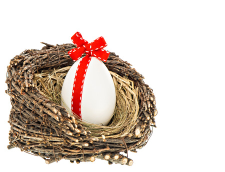 ribbon bow: white easter egg with red ribbon bow decoration in wooden nest isolated on white background