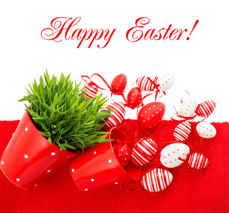 colorful white red painted easter eggs with green grass over table cover  festive composition with sample text Happy Easter  photo