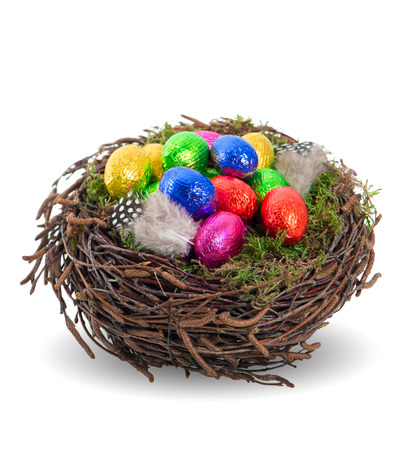 colorful chocolate easter eggs in nest on white background photo