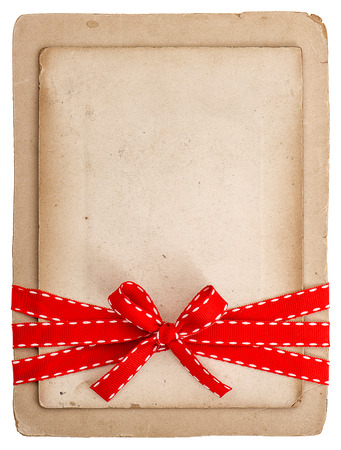 vintage card with red ribbon bow isolated on white  grunge paper background photo
