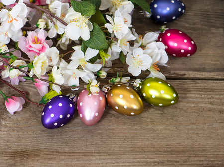 spring blossoms and easter eggs decoration on rustic wooden background photo