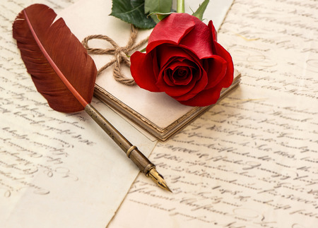 red rose flower, old letters and antique feather pen  sentimental vintage background  selective focus Stock Photo