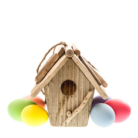 easter decoration with birdhouse and colorful eggs over white background photo