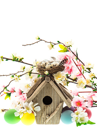 colorful easter decoration with birdhouse and eggs  spring apple and cherry blossoming photo