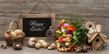 happy easter: vintage easter decoration with eggs and tulip flowers  chalkboard with sample text Happy Easter