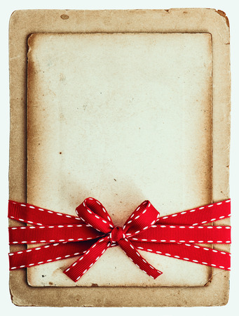 vintage card with red ribbon bow isolated on white background  grunge paper photo