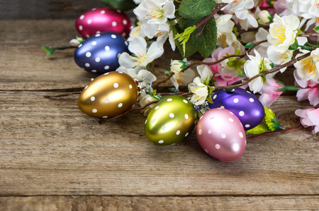 spring flowers and easter eggs decoration on rustic wooden background photo