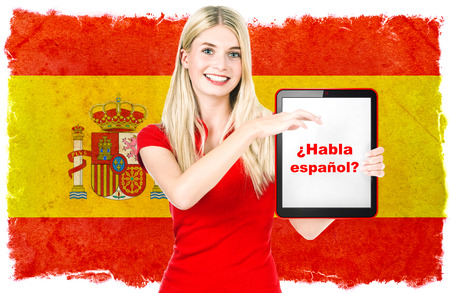 Young woman holding tablet pc  National flag of Spain at the background  Spanish language learning concept  Collage  Clip-Art photo