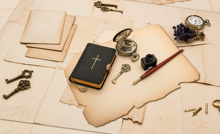 black bible book and vintage accessories with old cards and papers photo