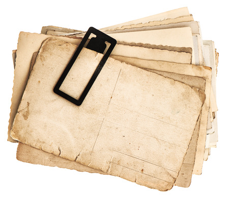 pile of old postcards isolated on white background  vintage paper sheets with clip  retro design photo