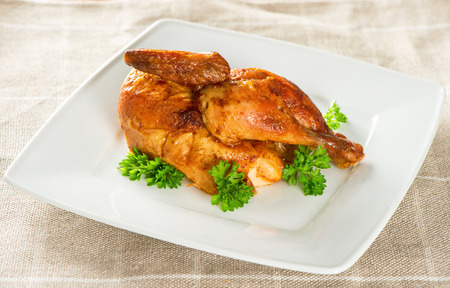 decoraton: grilled chicken decorated with green parsley herb on white plate  food ingredients