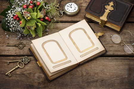 photo album cover: old photo album over rustic wooden background  vintage keys, clock, glasses  bouquet of orchid flowers  nostalgic picture Stock Photo