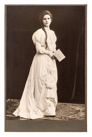 ヴィンテージのドレスを ca 1900 から聖書本の旧式な画像とポーズで若い女性