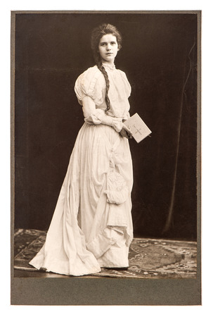 young woman in vintage dress posing with bible book  antique picture from ca  1900 Stok Fotoğraf
