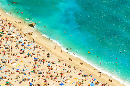 beach with tourists, sunbeds and umbrellas  travel top view