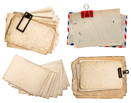 pile of old postcards isolated on white vintage paper sheets with clip  air mail envelope  retro design photo