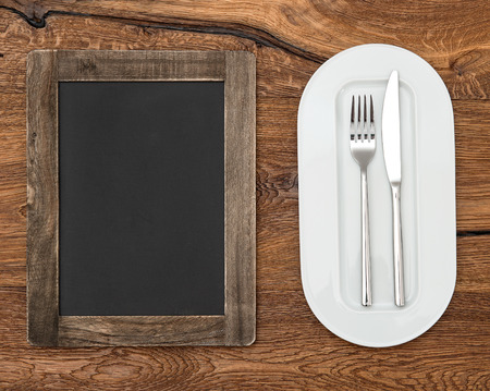 blackboard for menu on wooden table with white plate, knife and fork photo