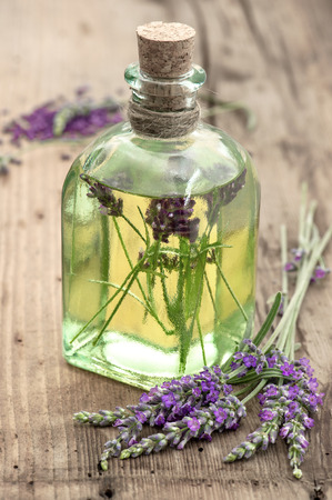 bottle of lavender oil with fresh flowers on wooden background apothecary herbs selective focus Stock Photo