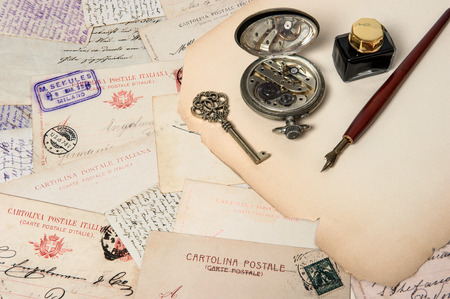 vintage accessories, antique ink pen, key, clock, old postcards and letters  scrapbook paper background photo