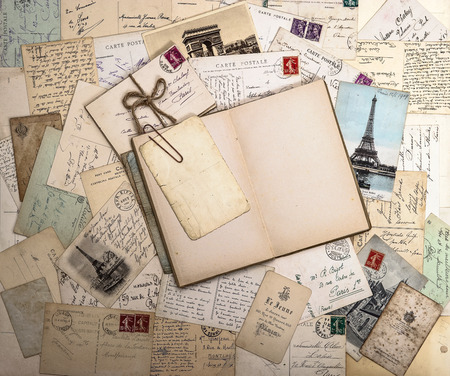 old letters, french postcards and empty open book  nostalgic vintage background
