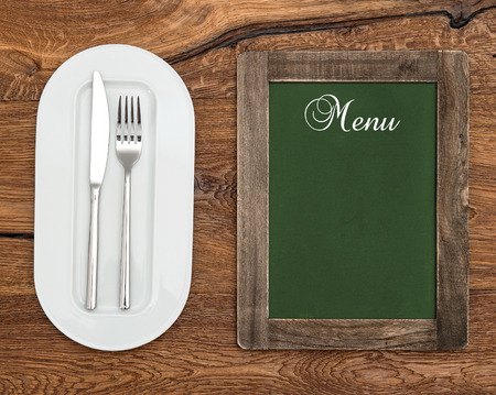 green chalkboard with white plate, knife and fork on wooden table  sample text Menu photo