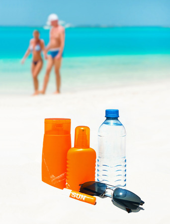 sun protection cream, water and sun glasses on the beach  travel background photo