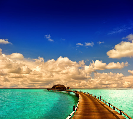 tropical sunset seascape  overwater bungalow with jetty with dramatic blue sky photo