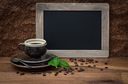 cup of coffee and antique blackboard  coffee leaves and beans  retro style image photo