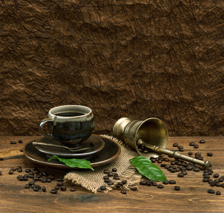 vintage still life with cup of coffee over brown wallpaper  retro style image photo