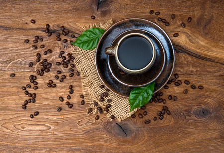 Cup of black coffee with beans and leaves on wooden background  Top view photo