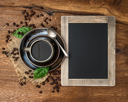 cup of coffee and antique blackboard  coffee leaves and beans  top view  selective focus photo