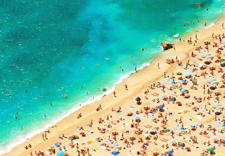 beach with tourists, sunbeds and umbrellas  sea travel destination  holidays background  top view