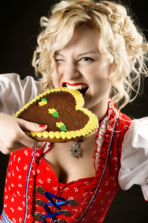portrait of funny girl in dirndl with typical oktoberfest  germany, bavaria, munich  cookie photo