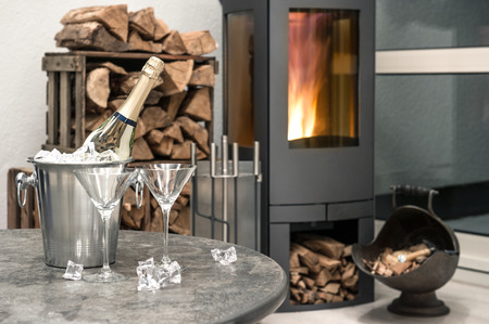 festive home interior wirh champagne, two glasses and fireplace  romantic arrangement  selective focus photo