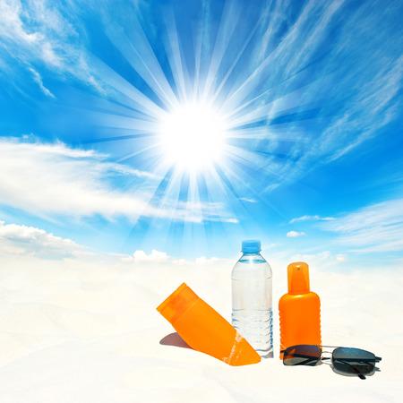 Crema protezione solare e una bottiglia di acqua sopra soleggiato cielo blu concetto di protezione solare Archivio Fotografico