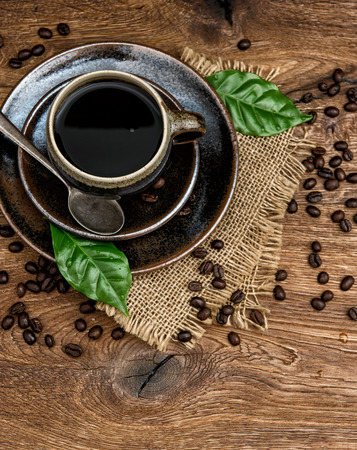 black coffee with beans and green leaves on wooden photo