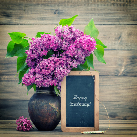 text pink: bouquet of lilac flowers on wooden blackboard with sample text Happy Birthday  retro style toned picture Stock Photo