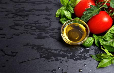 aceite de cocina: tomates y hojas de albahaca frescas con aceite de oliva en ingredientes negro de alimentos saludables