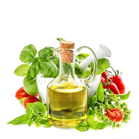 aceite de cocina: botella de aceite de oliva con hojas de albahaca fresca y tomates aislados en blanco ingredientes alimentarios italianos Foto de archivo