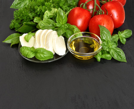 fresh basil, tomatoes, mozzarella and olive oil on black background  caprese salad ingredients photo