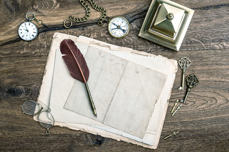 retro office tools and writing accessories on wooden antique keys, pocket watch, feather pen, compass  vintage style toned picture photo