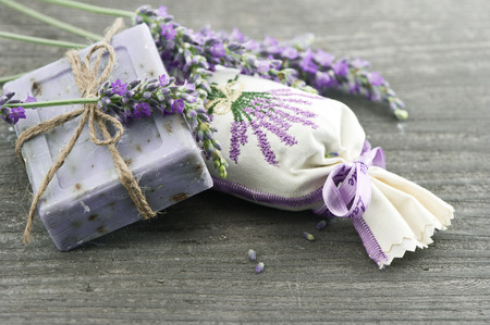 sachets: lavender soap and scented sachets with fresh flowers over wooden background
