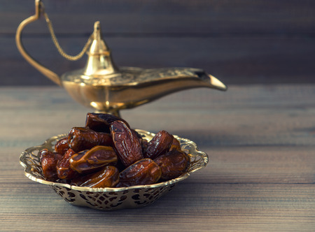 arabian food: Dates and golden arabian lamp on wooden background. Oriental food. Retro style toned picture